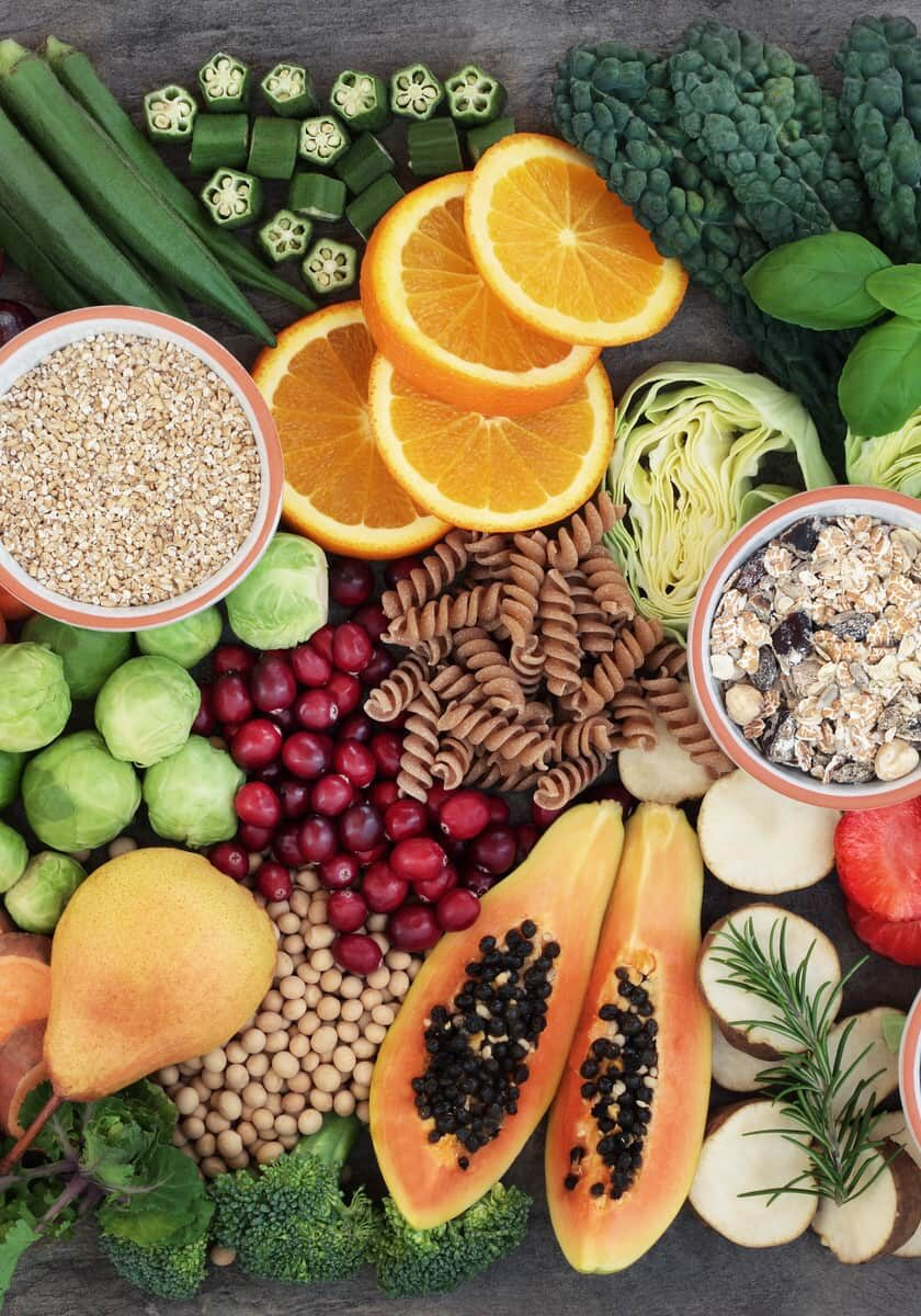 Health food concept for a high fiber diet with fruit, vegetables, cereals, whole wheat pasta, grains, legumes and herbs. Foods high in anthocyanins, antioxidants, smart carbohydrates and vitamins on marble background top view.